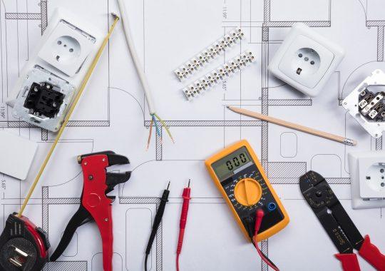 elektriciens gereedschap op een blauwdruk, tang, spanningsmeter en kabels